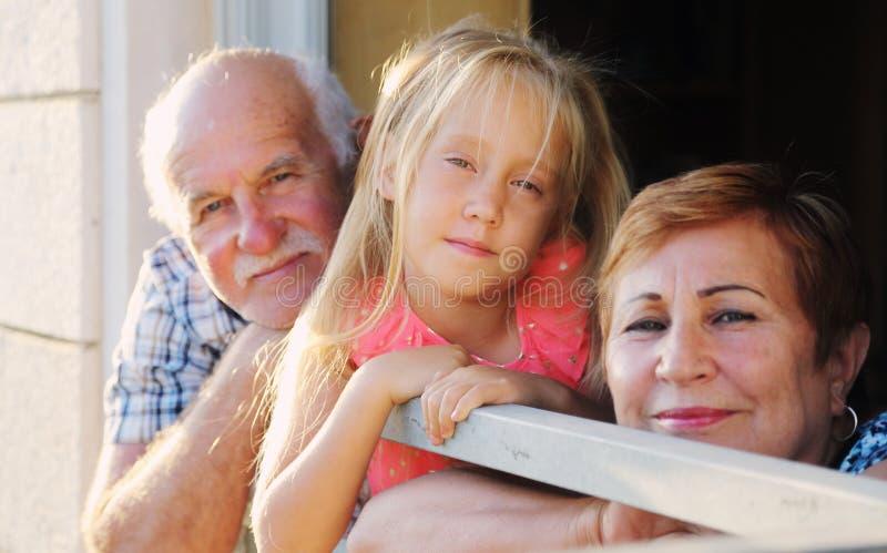 Grand-père et grand-mère tenant la petite-fille image stock