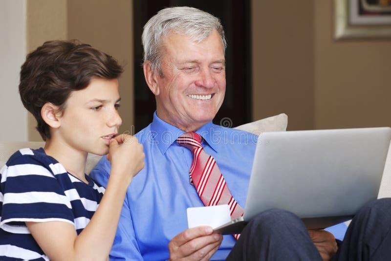 Grand-père et petit-fils avec l'ordinateur portable image libre de droits