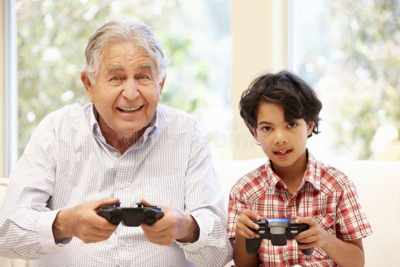 Grand-père et petit-fils jouant des jeux d'ordinateur photographie stock libre de droits