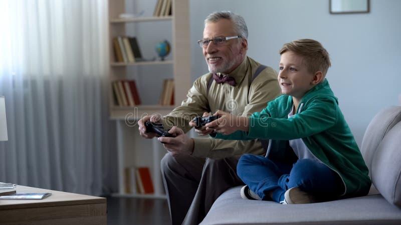 Grand-père et petit-fils jouant le jeu vidéo avec la console, temps heureux ensemble images stock