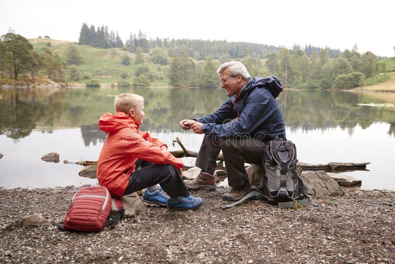 Grand-père et petit-fils s'asseyant au rivage d'un lac souriant ensemble, fin, secteur de lac, R-U photographie stock libre de droits