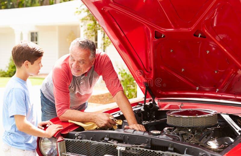 Grand-père et petit-fils travaillant à la voiture classique reconstituée photographie stock