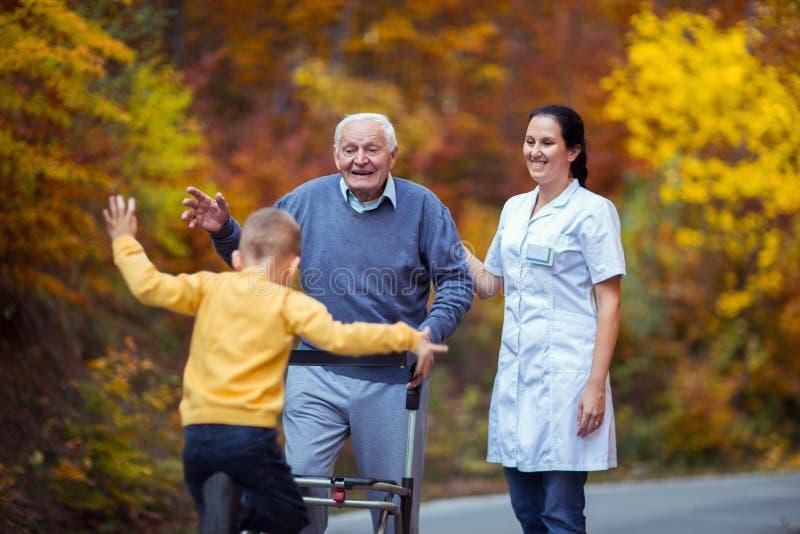 Grand-père handicapé gai dans le marcheur souhaitant la bienvenue à son petit-fils heureux photographie stock