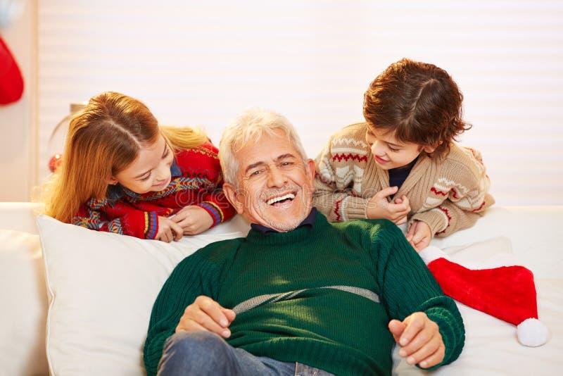 Grand-père heureux avec des petits-enfants à Noël photo libre de droits