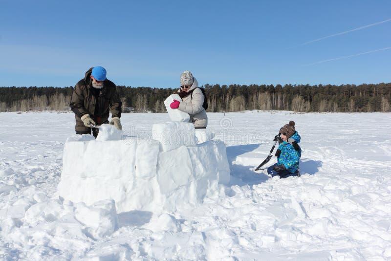 Grand-père, grand-mère heureuse et petit-fils construisant un igloo sur une clairière neigeuse en hiver photographie stock libre de droits