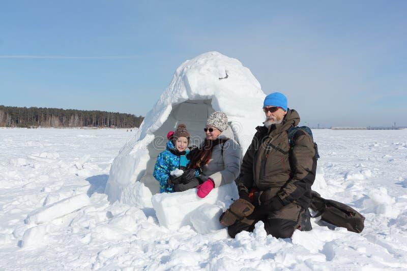 Grand-père, grand-mère heureuse et petit-fils s'asseyant près d'un igloo photographie stock libre de droits