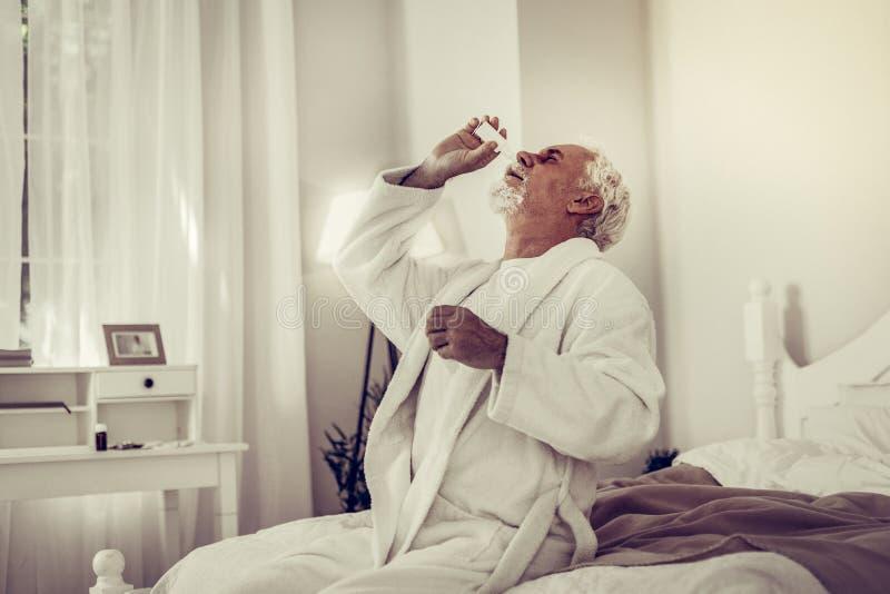 Grand-père malade vieillissant aux cheveux gris injectant des baisses dans le nez photo stock