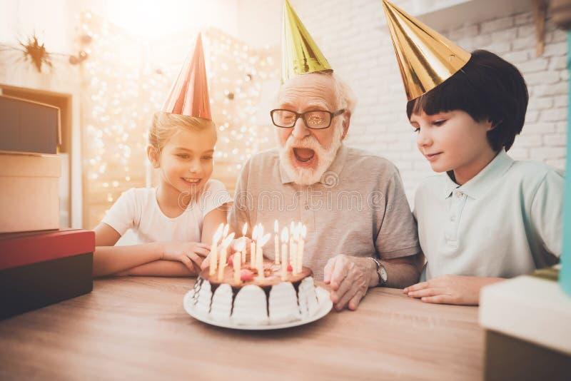 Grand-père, petit-fils et petite-fille à la maison Le grand-papa souffle des bougies sur le gâteau d'anniversaire photos libres de droits