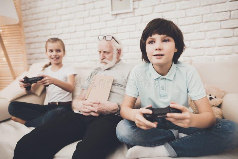 Grand-père, petit-fils et petite-fille à la maison Les enfants jouent des jeux vidéo et le grand-papa dort photographie stock libre de droits
