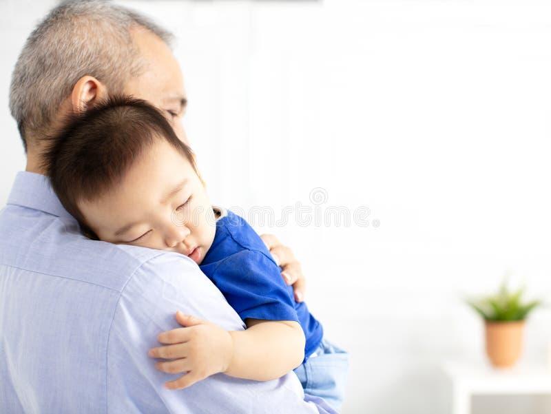 Grand-père tenant le bébé de sommeil de petit-fils photographie stock