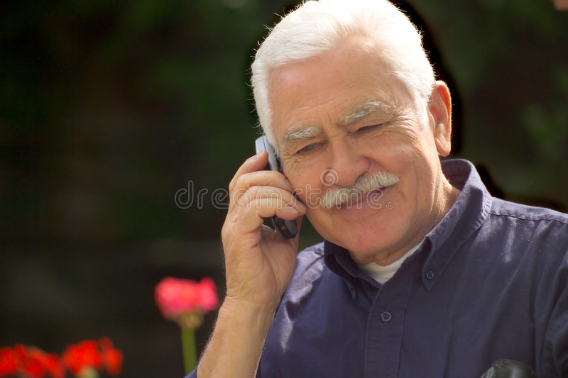 Grand pa and cellphone. Grey haired grandpa talking by cellphone