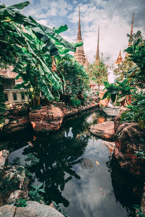 Grand Palace in Bangkok. Towers of Grand Palace reach into the Sky. Little lake inside the temple. royalty free stock images