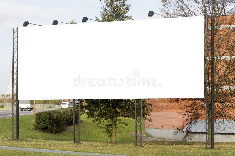 Grand panneau d'affichage vide près de la route avec le fond de vue de ville images stock