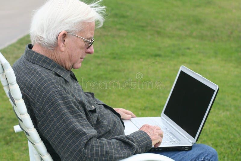 Grand-papa à l'aide d'un ordinateur portatif au golf photos libres de droits