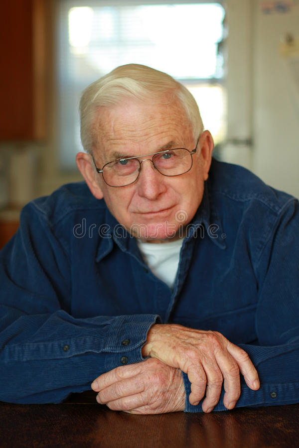 Grand-papa détendant à la table photo stock