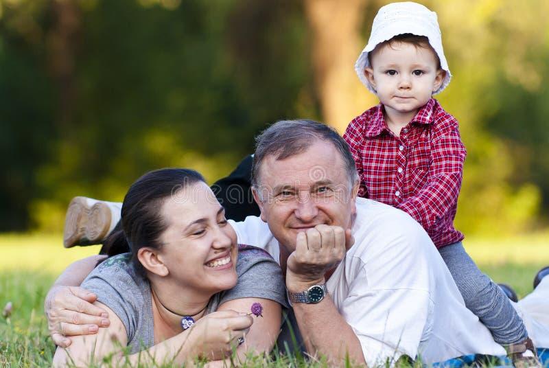 Grand-papa, descendant et nièce sur l'herbe image libre de droits