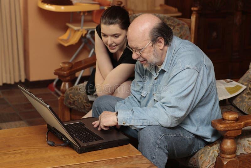 Grand-papa et enfant au PC d'ordinateur portatif image stock