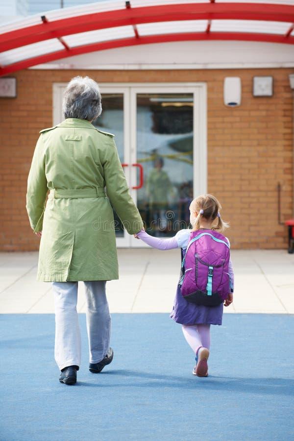 Grand-parent portant l'petit-enfant à l'école image libre de droits