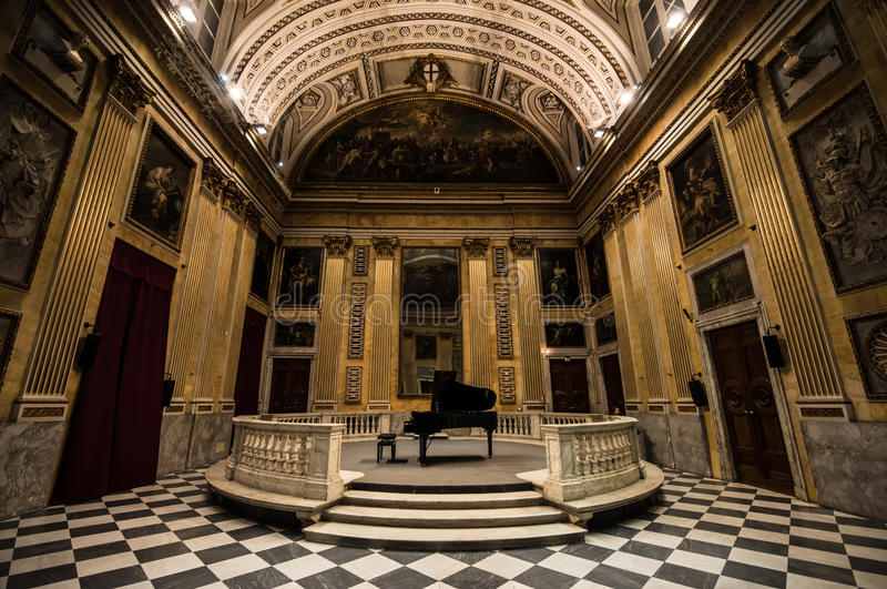 Grand Piano. A black grand piano in the middle of a music hall full of Renaissance and early Classic era painting and wall murals depicting various religious royalty free stock photos