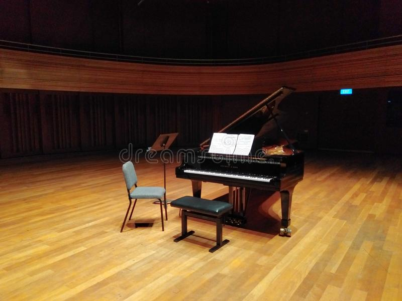 Grand piano on stage. In a concert hall, recitak, recital, rehearsal, nobody, music, musical, instrument, score, notes, university, cultural, centre, center stock photo