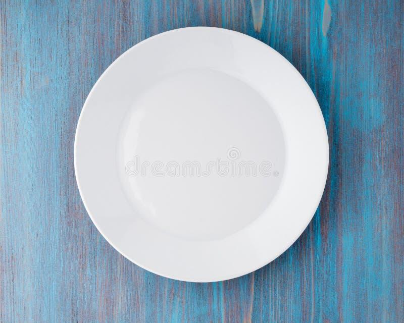 Grand plat blanc vide plat sur la table en bois bleue, vue supérieure images stock