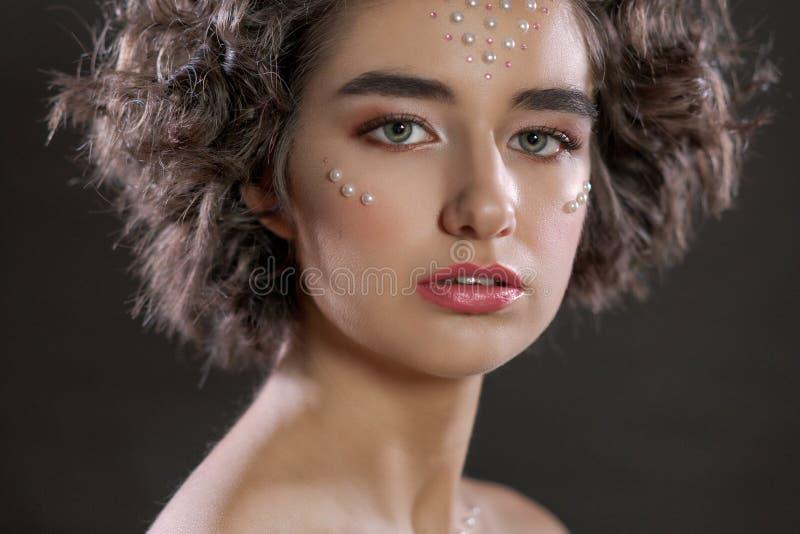 Grand portrait d'une belle femme avec un maquillage et des perles sur son visage, séance photos de beauté photos stock