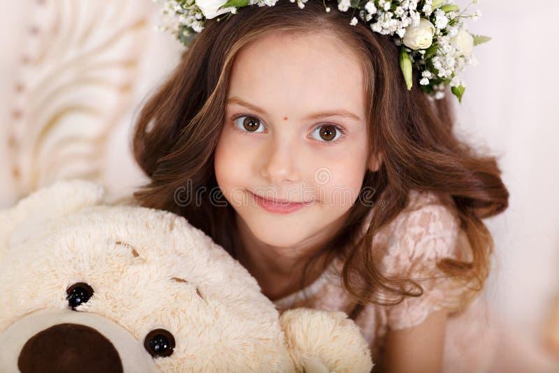 Grand portrait d'une fille mignonne avec le jouet lumineux regardant les cheveux foncés de caméra dans les boucles images stock