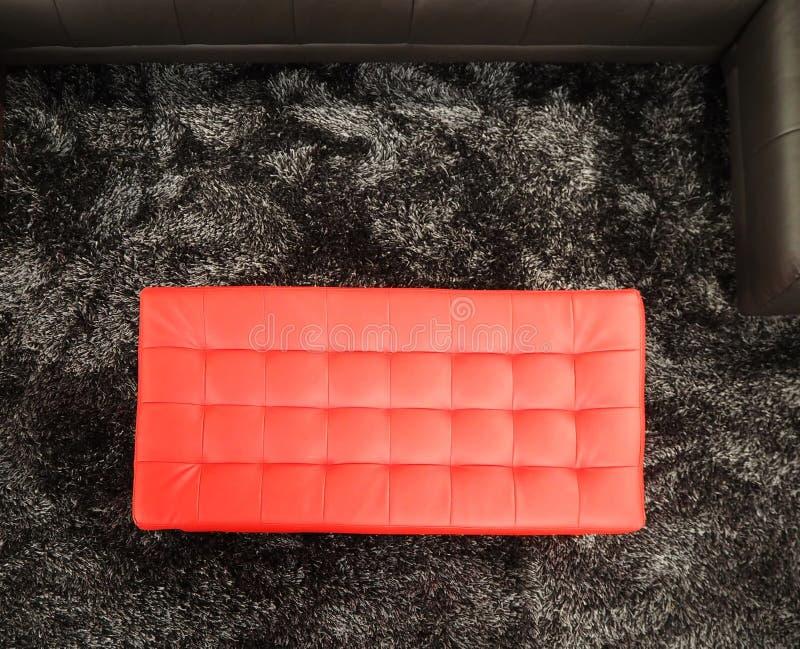 Grand pouf rouge en cuir de forme rectangulaire sur un tapis noir et gris photographie stock libre de droits
