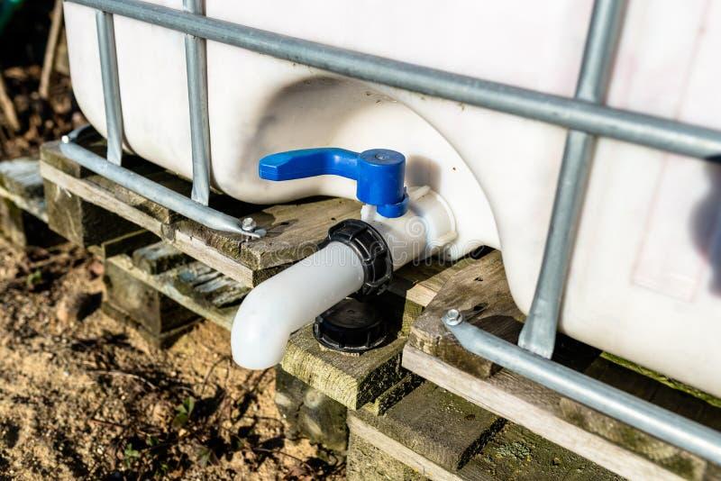 Grand réservoir liquide industriel avec une capacité de 1000 litres, 265 gallons avec un gril protecteur en métal Plan rapproché  photos stock