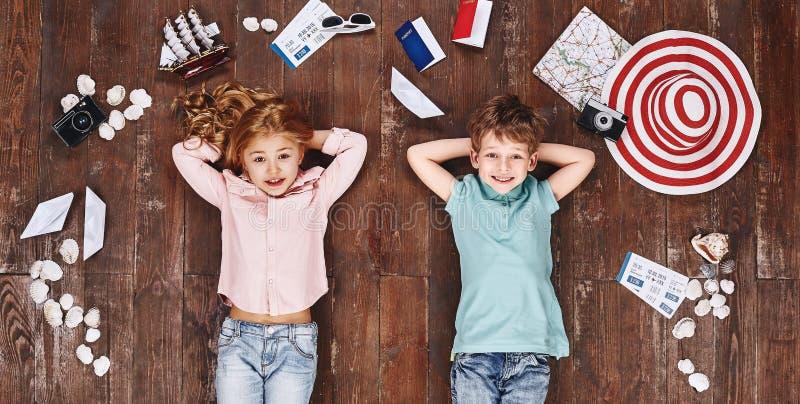 Grand rêveur Enfants se trouvant près des articles de voyage, regardant la caméra et le sourire photos stock