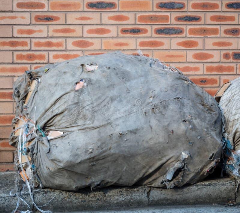 Grand sac de tissu des déchets ou de la réutilisation du côté de la route près du mur de briques images stock