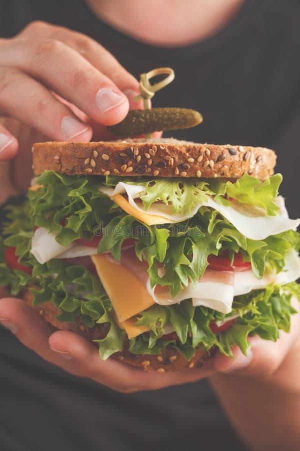 Grand sandwich avec de la viande, le fromage et les légumes frais dans la main masculine photographie stock