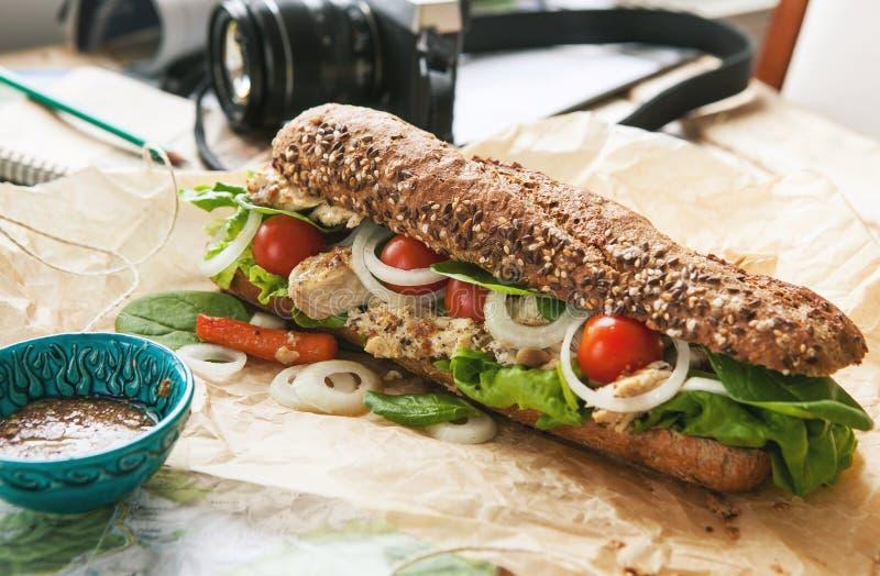 Grand sandwich avec le poulet sur la table de photographe de voyage images libres de droits