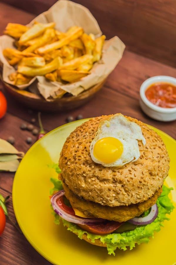 Grand sandwich - hamburger d'hamburger avec le poulet, fromage, tomate Sur un fond rustique en bois Plan rapproché photographie stock libre de droits