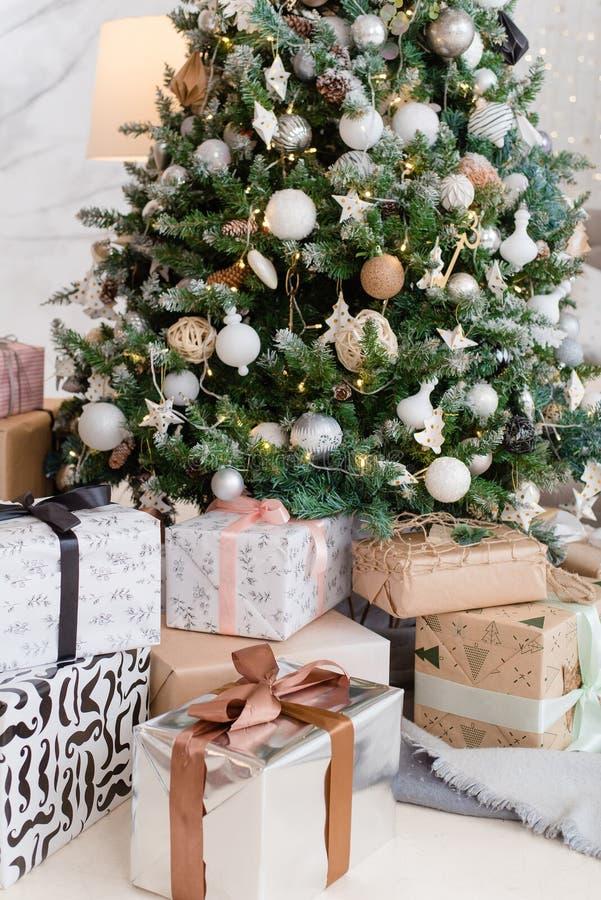 Grand sapin de Noël avec cadeaux dans une salle blanche photo stock