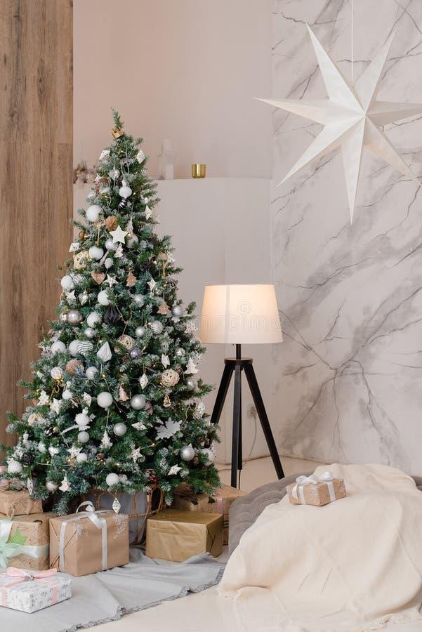 Grand sapin de Noël avec cadeaux dans une salle blanche images stock