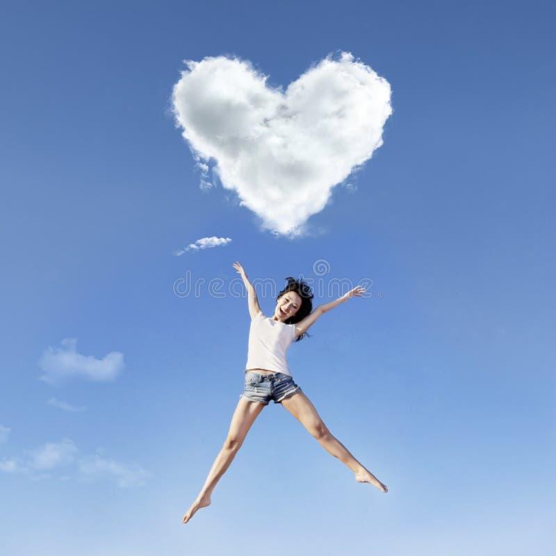 Grand saut de fille sous des nuages de coeur image libre de droits