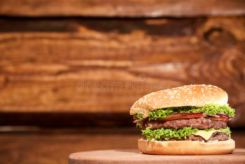 Grand, savoureux, juteux et frais hamburger avec de la viande, les légumes et la feuille de salade placée sur un conseil en bois photos stock