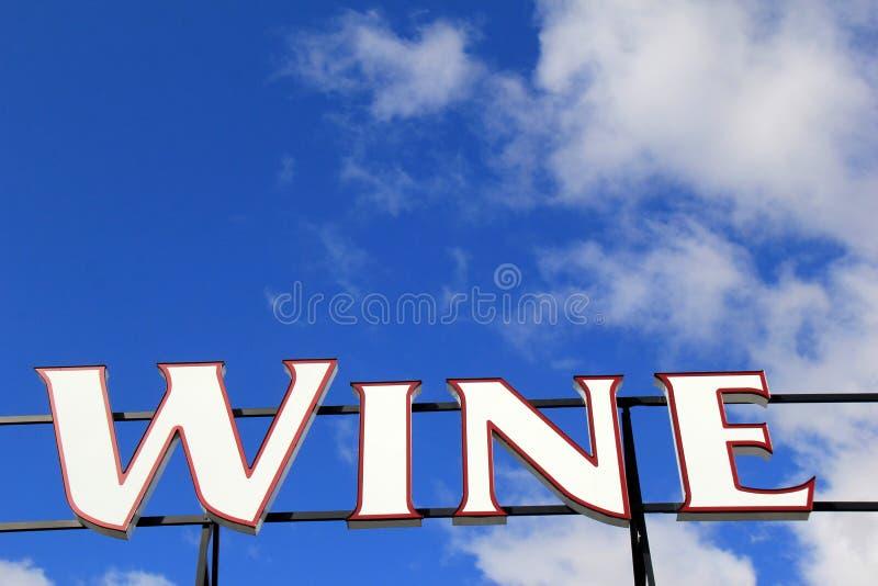 Grand signe avec des lettres définissant le vin de mot aux gens passant par image stock