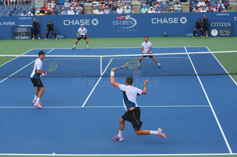 Grand Slam champions Mike and Bob Bryan (at the front) during US Open 2014 round 3 doubles match. NEW YORK -SEPTEMBER 1, 2014: Grand Slam champions Mike and Bob stock images