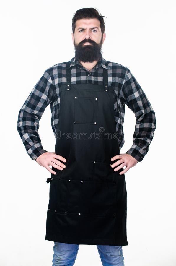 Grand style de barbe qui semble fantastique Homme brutal dans le tablier de travail Homme barbu avec la coupe de cheveux ?l?gante photographie stock libre de droits