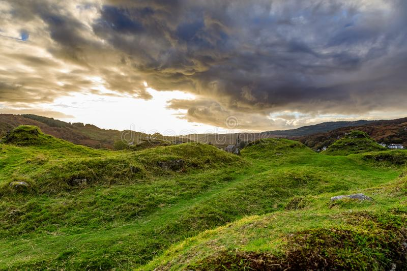 Grand swirling clouds before sunset over rolling green grass cut short by sheep near the Royal Castle of Tarbert in Argyll and royalty free stock photography