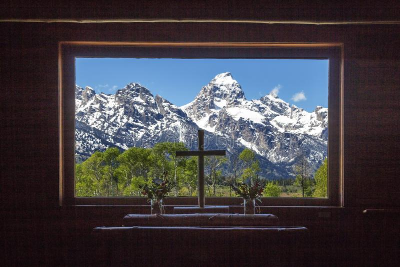 Grand Teton peaks view from the wooden Chapel of Transfiguration window. With a Christianity cross in the center stock photography