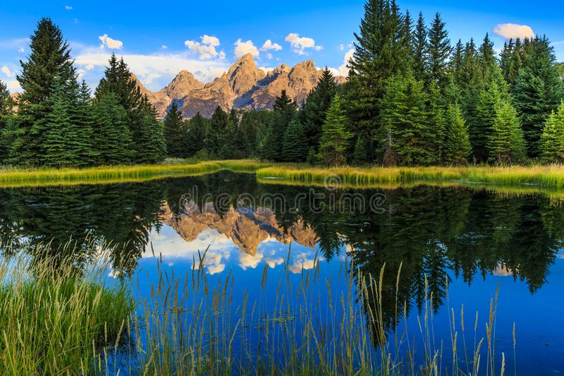 Grand Teton Reflections in Snake River. This image is of the Grand Teton Mountains reflected in the Snake River at Sunrise. This photograph was taken in Jackson stock photography