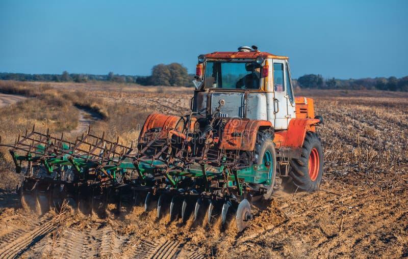 Grand, vieux, beau tracteur labourant la terre sur le champ après des tournesols de récolte d'automne de récolte photos stock