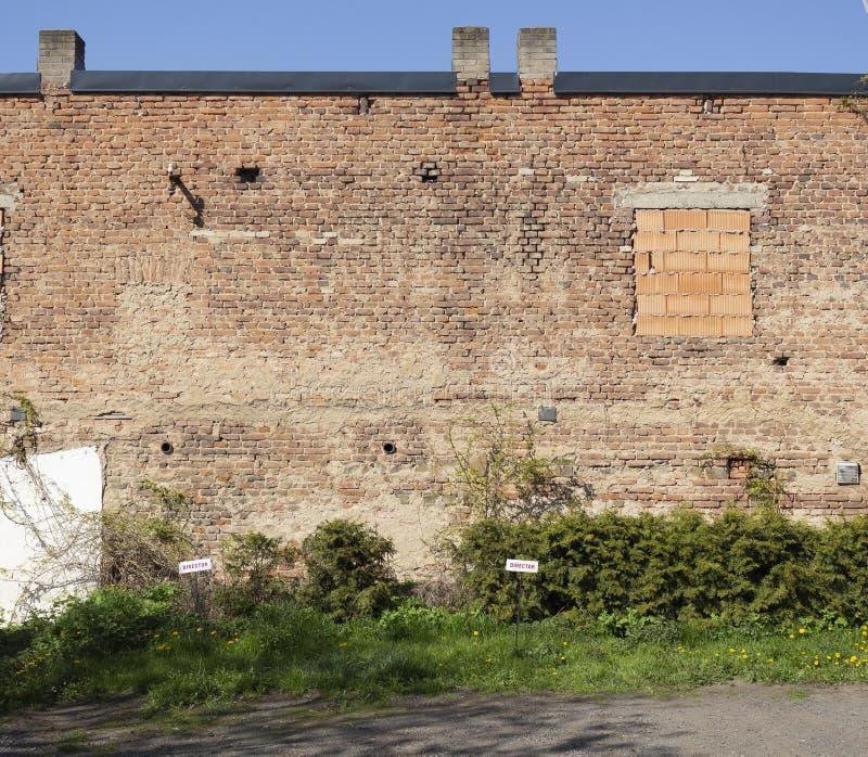 Grand vieux mur de briques avec la fenêtre aveugle et deux les directeurs garant des signes photo stock