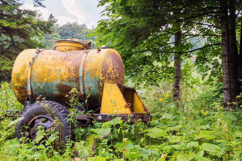 Grand vieux réservoir d'eau jaune de baril d'arrosage et de lait image stock