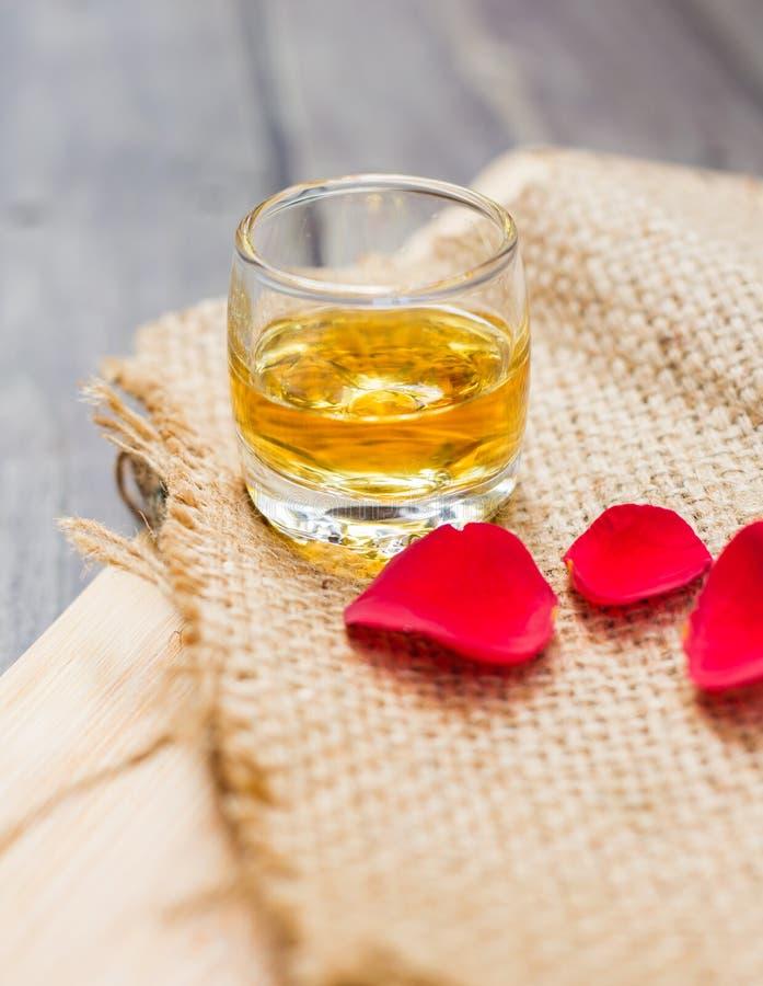 Grand whiskey avec des pétales de rose photos stock