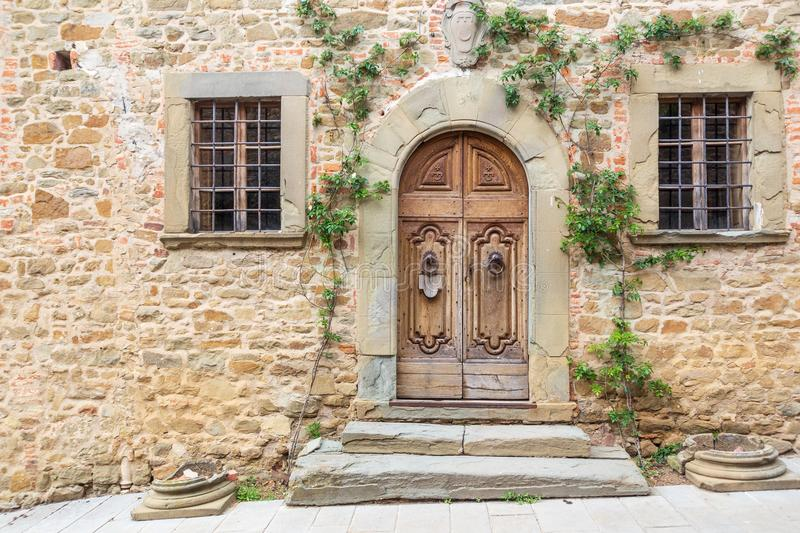 Grand, wooden door graced with green vines in the medieval town of Volpaia. stock images