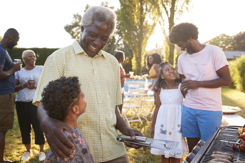 Grandad и папа разговаривая с детьми на барбекю семьи стоковое изображение